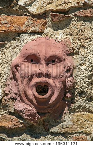 Close-up of clay mask attached to the wall in Colle di Val d'Elsa. A graceful village with its historic center preserved and known by its crystal production. Located in the Tuscany region
