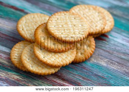 Close-up of a of salted crackers on an old wooden table.