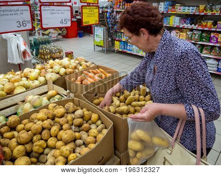 Voronezh, Russia - May 25, 2017: An elderly woman is picking potatoes in a package