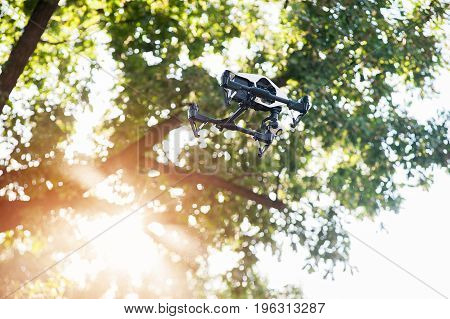White drone with digital camera flying in sky on background of tree