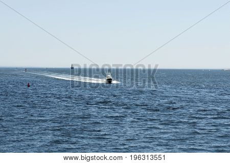 Sportfishing boat hurrying toward New Bedford inner harbor from Buzzards Bay