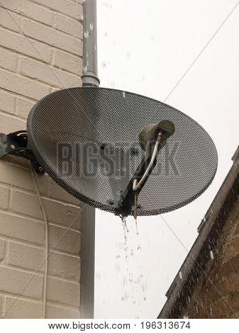 raining water coming down over a black satellite dish in garden; Essex; UK