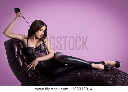 Sexy elegant woman lies in a corset on a leather sofa. Sensual woman posing on couch. Copy space