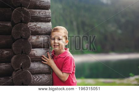 Young boy hugging a tree house near the lake