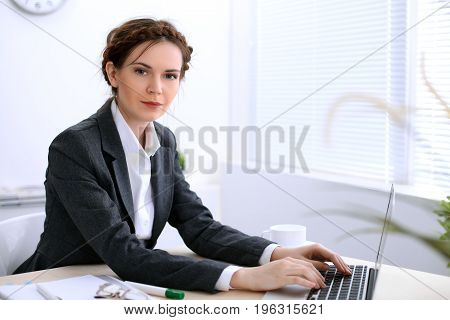 Business woman with a cup of coffee is sitting at the table and typing on a laptop computer in the white colored office . Ukrainian hair styling. Independence and success concept.