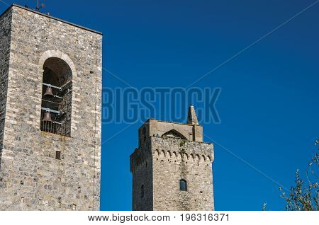 View of the stone towers with bells on the sunny blue sky at San Gimignano. An amazing medieval town famous for having several towers in its historical center. Located in the Tuscany region