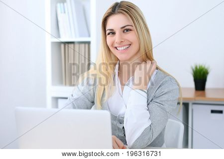 Young business woman or student girl sitting at office workplace with laptop computer. Home business concept.
