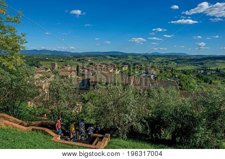 San Gimignano, Italy - May 13, 2013. View of people descending staircase between trees at San Gimignano. A medieval town famous for having several towers in its historical center. Tuscany region