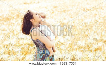 Beautiful woman holding baby. Mother and son walking in a meadow at summer.