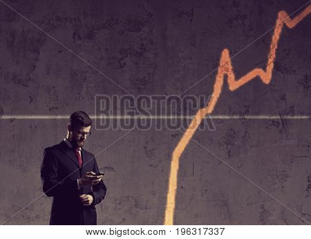 Businessman with smartphone standing over diagram background. Business, office, success, concept.