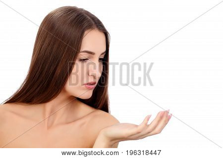 Beauty Spa Woman with perfect skin Portrait. Beautiful Brunette Spa Girl showing empty copy space on the open hand palm for text. Proposing a product. Gestures for advertisement. Isolated background.