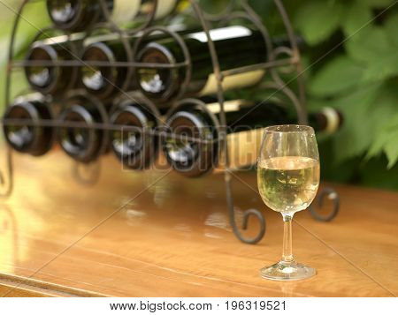 Glass of white wine in focus and a bottles holder in the background outdoor garden party