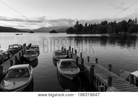 Tranquil dusk scene of Boats moored in piers in Lake Windermere in Cumbria- black and white photo