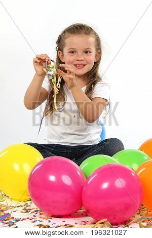 Cute little child with balloons, confetti and streamers
