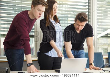 Serious young business people using laptop in office