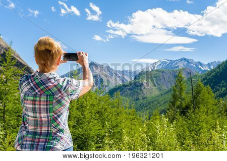 Woman photographing landscape on smartphone. Eastern Sayan, Siberia, Russia
