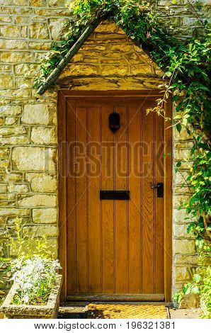 Stylish Entrance To A Residential Building, An Interesting Facade Of The Old Stone Wall, Old Wooden