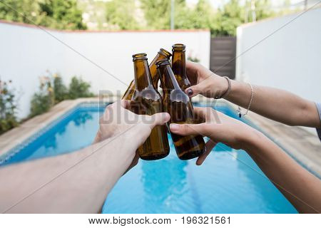 Hands of some friends toasting with beer bottles in the pool at a party celebrating the holidays.