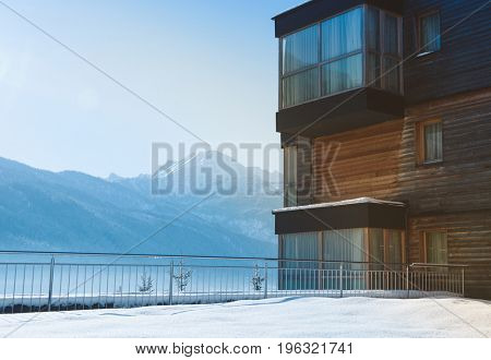 Timber chalet or office in a winter landscape with fresh snow and high alpine peaks obscured by light mist