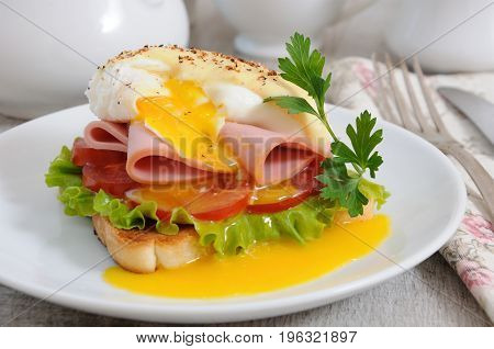 Toast with slices of ham and tomatoes Benedict egg with Dutch sauce.