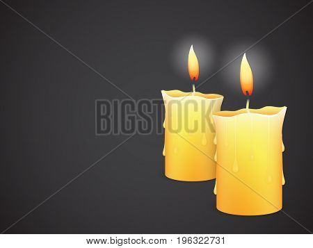 two burning candles on dark black background