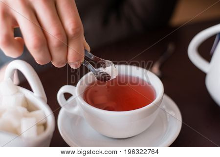 piece of sugar stuck from a heap and will throw in a glass of tea