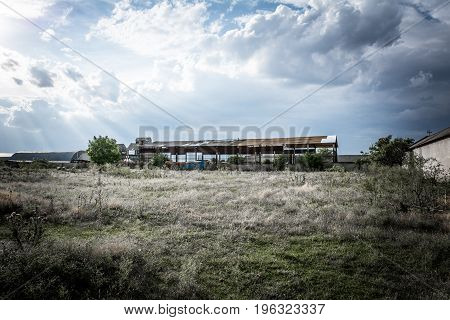 An Abandoned Building For Drying Grain On The Background Of An Evening Overcast Sky