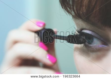 Make Up Vanity 3: self portrait of a woman applying mascara, shallow depth of field put attention on her eye