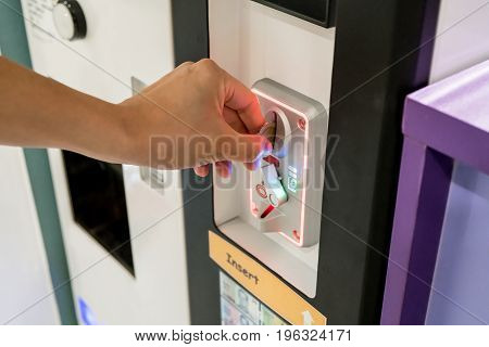 Woman hand inserting coins into vending machine. Selective focus
