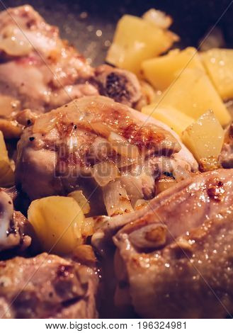 Chicken is fried with potatoes in a frying pan close up