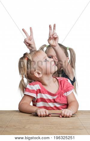 Two little girls play at the school desk. One makes the other horns. Isolated over white background