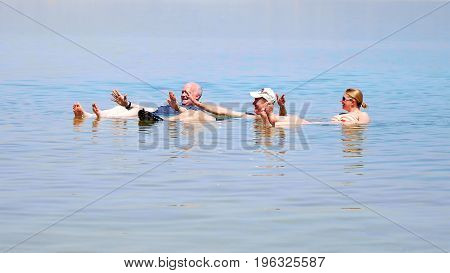 Dead Sea, Israel - May 22, 2017: People are bathing and swimming in the Dead Sea. The salinity of the dead sea water makes people floating in water. Dead sea is located between Jordan and Israel.