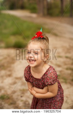 Cheerful girl in a light dress in a clearing in the forest