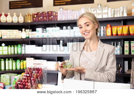 Beautiful young woman with perfume in beauty store