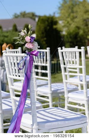 Decoration of the white chair with Eustoma flowers and ribbons for exterior wedding ceremony