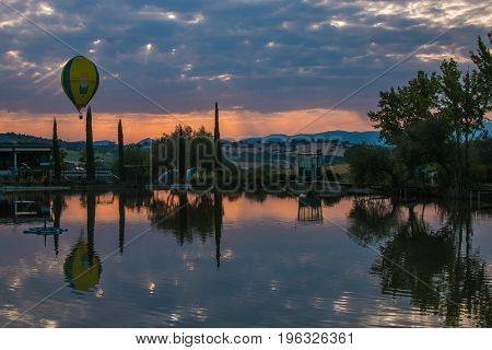 GUALDO CATTANEO, ITALY - JULY 21, 2017: Hot air balloons flying over umbria lake during italian competition at sunrise