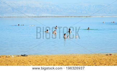 Dead Sea, Israel - May 22, 2017: Dead sea beach panoramic shot. People are bathing and swimming in the most salty sea on the planet. Dead sea is located in Middle East between Jordan and Israel.