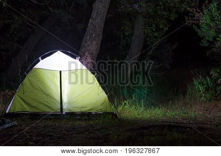 The tent glows at night in the forest camping. Tourism tent close-up.