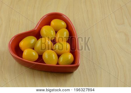 Lower acid yellow cherry tomatoes in red heart shaped bowl on wooden table