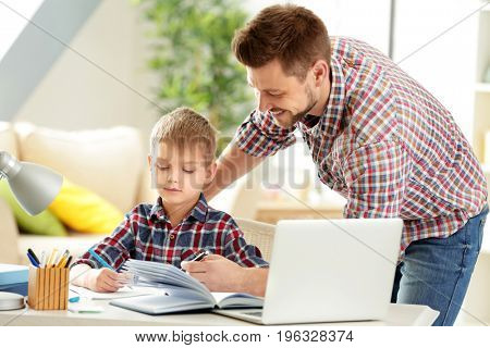 Father and son doing homework together at home