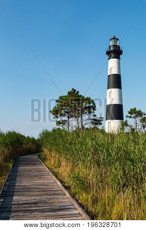 Wooden boardwalk through marshland leading to the historic Bodie Island lighthouse on the Outer Banks of North Carolina.