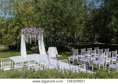Wedding ceremony in white, violet, blue, pink colors outdoors in wide format