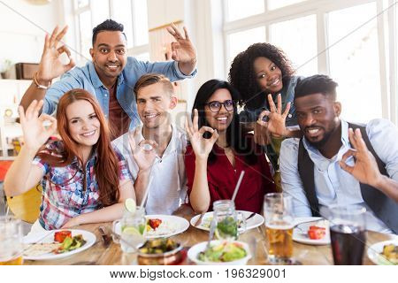 eating, food and people concept - group of happy international friends showing ok hand sign at restaurant table