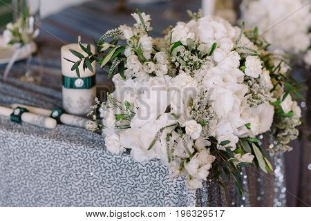 White floral decoration of the table on silver cloth with candles for the wedding ceremony