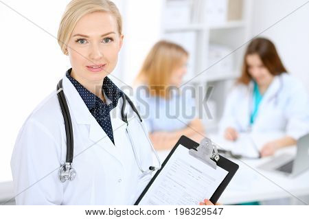Female doctor smiling on the background with patient and his physician in hospital.
