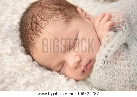 Sleeping newborn baby boy on soft plaid at home