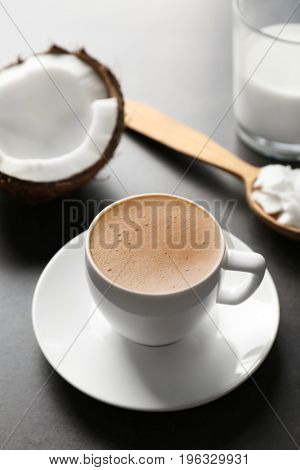 Cup of tasty coconut coffee, nut and spoon with butter on table