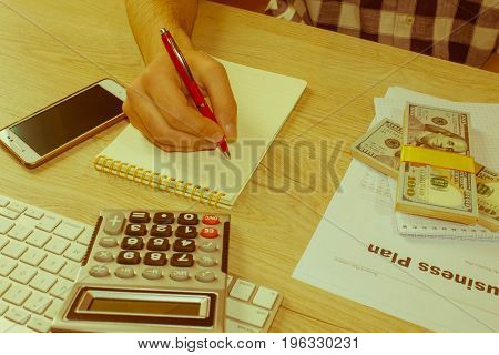 Man taking notes money and calculator on the table. Men with fountain pen and banknotes on a wooden table. Business concept - Retro color