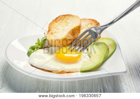 Eating delicious over easy egg with toasts and avocado on kitchen table
