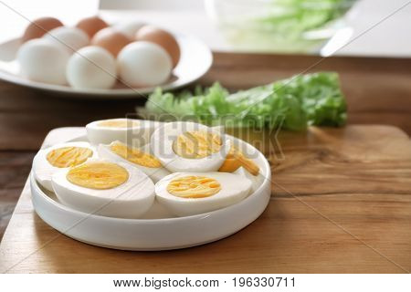 Ceramic plate with hard boiled eggs on wooden surface. Nutrition concept